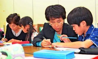 子どもを教える齋藤佳代さん(右から2人目)=名護市・大中公民館