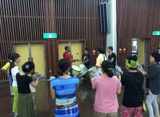 熱心に打楽器の指導をするヴァグネル先生(中央奥)=10月、那  覇市民会館中ホール