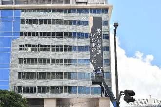 10時からシートの貼り付けが始まった=30日午前11時間すぎ、那覇市・沖縄タイムスビル