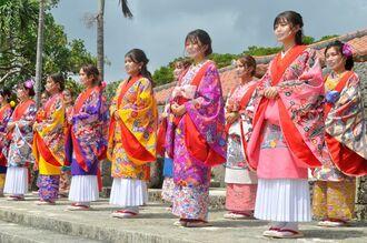 琉装のファッションショーが開かれ、観光客らがカメラを向けた=18日、南城市のおきなわワールド