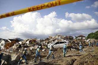 土砂崩れ現場の捜索に向かう警察官=9日午後4時57分、広島県熊野町(共同通信)