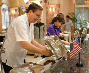 アメリカンビーフを使った料理を取り分けるマグルビー氏(左)や来店客=11日、名護市・オキナワマリオットリゾート&スパ