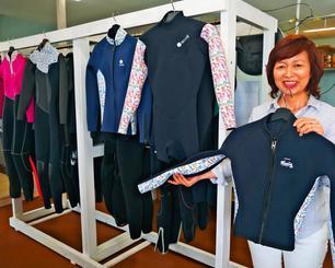 琉球紅型を特殊プリントした生地で、ウエットスーツを製造するオキナワブレッシングの角倉真理店長=14日、うるま市の同店