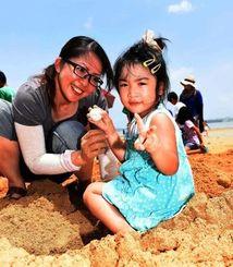 砂浜を掘って宝さがし。「ボール見つけたよ」とピースサインをする女の子