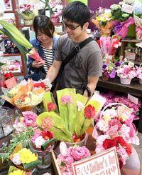 母の日に贈る花を選ぶ買い物客=13日、那覇市久茂地のオランディアガーデンパレット久茂地店(下地広也撮影)