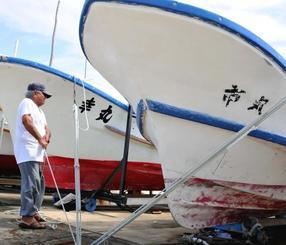 陸揚げした漁船をロープで固定する漁師=28日、石垣市新栄町・石垣港