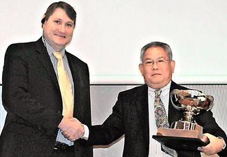 ショーン・キュニアル副社長(左)か記念カップを受けた高橋社長=21日、宜野湾市・ラグナガーデンホテル