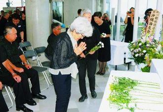 祭壇に花を手向ける遺族や関係者ら=日、豊見城市豊見城・海軍壕公園ビジターセンター