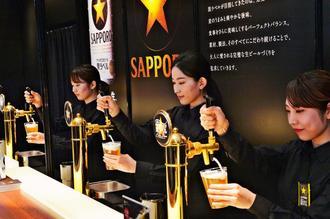 内覧会でビールを注ぐ女性スタッフ=20日午後、那覇市久茂地・タイムスビル