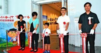 原画展のテープカットをする安里有生君(中央)と長谷川義史さん(右から2人目)=23日、糸満市の県平和祈念資料館