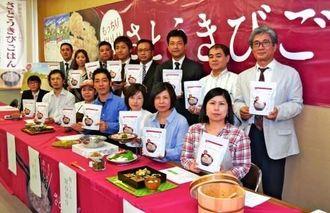 「さとうきびごはんの素」をPRする仲程俊和社長(後列右から3人目)と提供・販売店舗の代表者ら(前列)=20日、県庁
