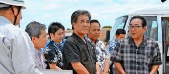 島袋村長(右)とドラム缶落下現場を視察する高良副知事(中央)=21日、伊江村