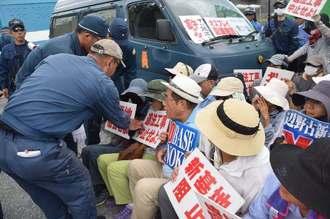 新基地建設に抗議して座り込む市民らを排除する機動隊員=30日正午、名護市辺野古の米軍キャンプ・シュワブ工事車両用ゲート前
