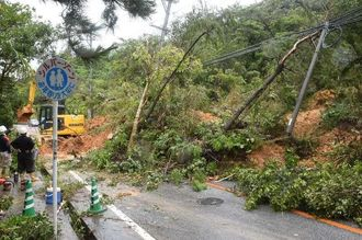 約20メートルに渡って土砂が崩れ、全面通行止めになった国道331号。土砂崩れの影響で折れた電柱=21日午前11時38分、東村平良