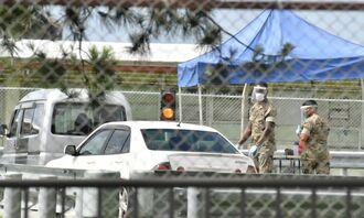 検温所で、基地内に入った車両の運転手らをチェックする米兵=9日午後、金武町・米軍