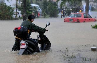 冠水した道路が通れず、バイクを押して歩道を歩く市民=26日午前9時58分、石垣市真栄里(新垣玲央撮影、画像の一部を加工しています)