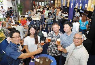 サントリーのザ・プレミアムモルツ4種のビールを味わう来場者=3日午後、那覇市久茂地・タイムスビル1階エントランス