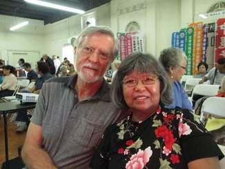 ウチナーンチュ大会の説明会場、ロサンゼルス郊外ガーデナの北米沖縄県人会館で寄り添う春子さん(右)と夫のロナルドさん