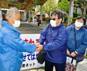 具志堅隆松さん(左)を激励する浜田哲二さん(中央)と妻律子さん=5日、那覇市