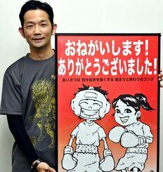 最優秀賞のポスターを手にする大山朝之さん。全国のボクシングジムに掲示される=沖縄タイムス社