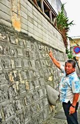 学校を囲うブロック塀の点検箇所を説明する仲盛康治校長=20日、那覇市・寄宮中学校