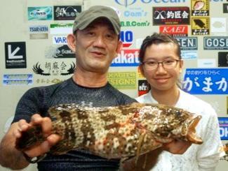 北谷海岸で48・7センチ、1・92キロのミーバイを釣った比嘉良行さん(左)=6月25日