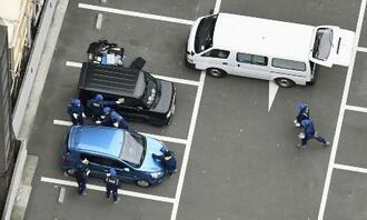 現金約3億8千万円が強奪される事件があった駐車場を調べる捜査員=4月、福岡市