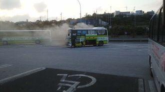 煙を上げる観光バス=9日午後6時ごろ、沖縄自動車道中城PA(宮平守光さん提供)