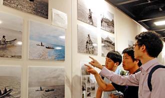 人工知能で色付けされた写真に見入る海外の学生ら=28日、那覇市久茂地・タイムスギャラリー