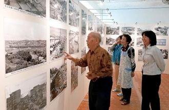 戦後の市場の変遷が分かる写真をなつかしそうに眺める市場関係者=牧志・ガーブ川中央商店街2階ギャラリー