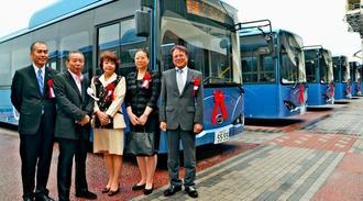 県内で初めて導入された電気バスのお披露目に出席した沖縄シップスエージェンシーの松田美貴会長(左から2人目)ら=1日、那覇市若狭の那覇港クルーズターミナル