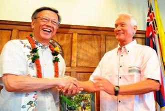 かりゆしウエアに着替え、コールドウェルホノルル市長(右)と握手する翁長雄志知事=2016年5月10日、ホノルル市庁