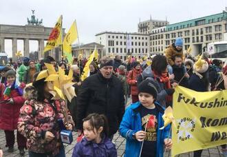 10日、ベルリンで原発の即時停止や核兵器の廃絶を求め、デモ行進する市民ら(共同)
