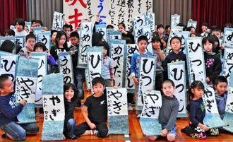 書き上げた作品を手に記念撮影に納まる「新春かきぞめ大会」の参加者たち=糸満市西崎町の光洋小学校