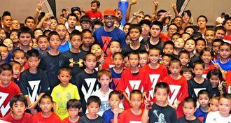NBAのスター選手ジョン・ウォール(中央)と記念撮影をする子どもたち=宜野湾市立体育館