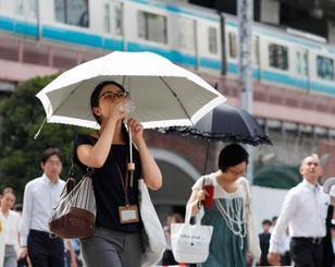 厳しい暑さの中、JR新橋駅前を歩く女性=23日午前