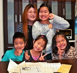 思いもよらない手紙や「お年玉」を喜ぶ(後列左から)上江洲咲希さんと長女・星奈さん、(手前左から)長男・瀧心君、三女・莉帆奈さん、次女・萌奈さん=那覇市真地の自宅で