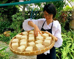豆腐をざるに並べて天日で干す松島よう子さん。干した豆腐は約3分の2の大きさに小さくなり、きつね色に変色しぬめりが出る=那覇市首里