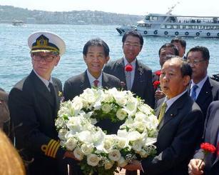 和歌山県沖に沈没したトルコ軍艦「エルトゥールル号」の追悼行事後に花輪を持つ自民党の二階幹事長(右)ら=30日、トルコ・イスタンブール(共同)