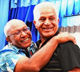 親類が見つかったことを喜ぶベルナール・イケハラさん(右)=25日、那覇市久米・県青年会館