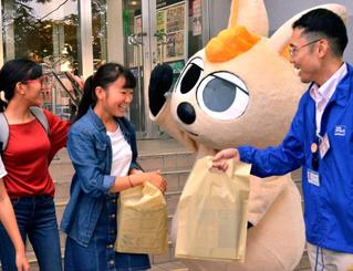 ワラビーから見本紙を受け取り、笑顔を見せる学生ら(左)=13日、イオン那覇店