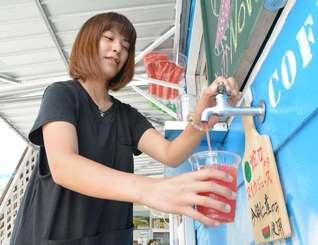 蛇口をひねり、スイカジュースを注ぐ女性=5日、今帰仁村天底・橋の駅リカリカワルミ