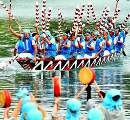 海に漬かった女性たちが太鼓を鳴らしながら爬龍船(はりゅうせん)を迎える=9日、大宜味村塩屋(金城健太撮影)