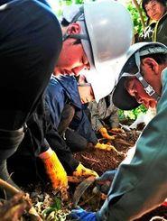 頭蓋骨が出てきた付近を丁寧に掘り返していく県外の大学生たちと県遺族連合会のメンバーら=2013年2月、糸満市喜屋武
