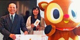 上地夏姫さんにスマートフォンを贈った北川社長(左)=那覇市松山・沖縄セルラー本社(同社提供)