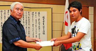 LGBT政策の請願書を県議会の新里米吉議長に提出する平良亮太さん(右)=2016年9月28日、県議会議長室