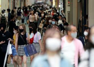 大阪・ミナミを歩くマスク姿の人たち=16日午後