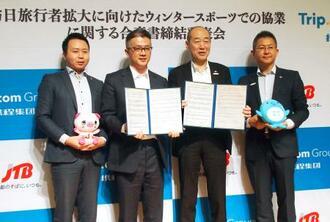トリップドットコム・グループ幹部と協業の合意書を交わしたJTBの坪井泰博執行役員(右から2人目)=3日午前、東京都品川区