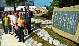 「生誕之地碑」完成を喜ぶ、山内徳信会長(左列先頭)と関係者=25日、読谷村瀬名波