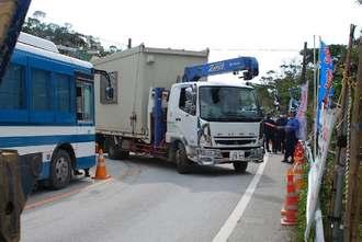 警備員や機動隊が先導する中、プレハブ小屋を運び出すトラック=16日正午すぎ、東村高江付近